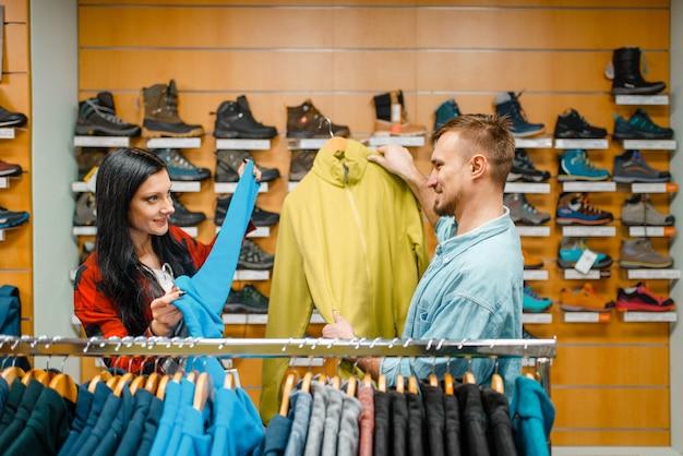 Пара, выбирая велосипедные костюмы, спортивный магазин