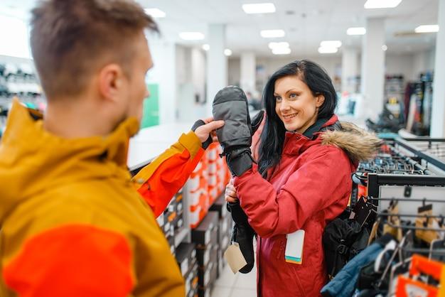 Couple choosing gloves for ski or snowboarding