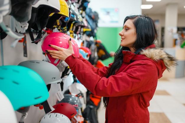 Couple choosing helmets, shopping in sports shop