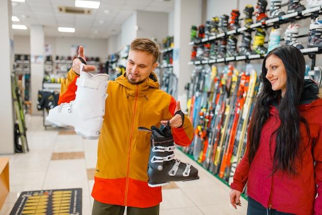Couple choosing ski boots, shopping, sports shop