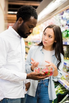 Couple choosing strawberry in grocery store