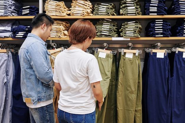 Couple choosing trousers in shop