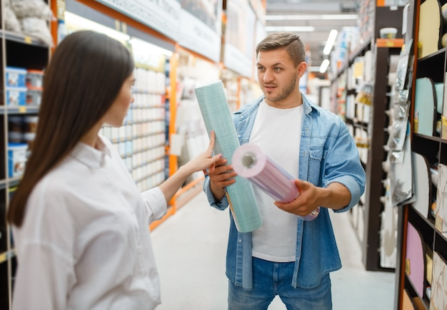 Couple choosing wallpapers color in hardware store