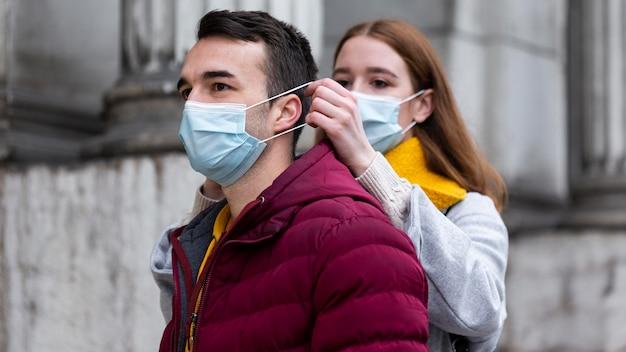 Coppia in città indossando maschere mediche insieme