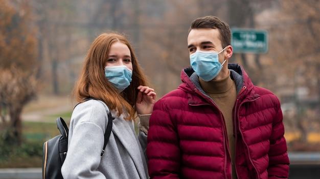 Coppia in città che indossa maschere mediche