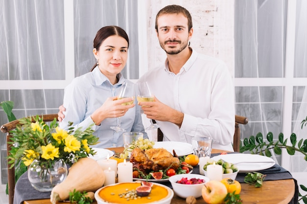 Couple clanging glasses at festive table