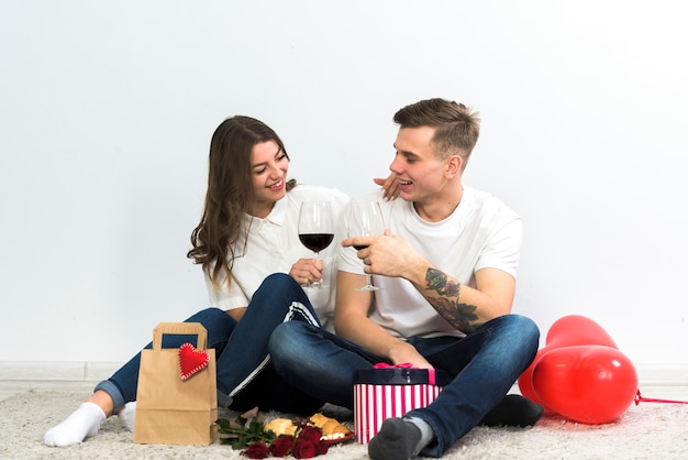 Couple clanging glasses of wine on floor