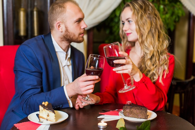 Couple clanging wine glasses at table in restaurant