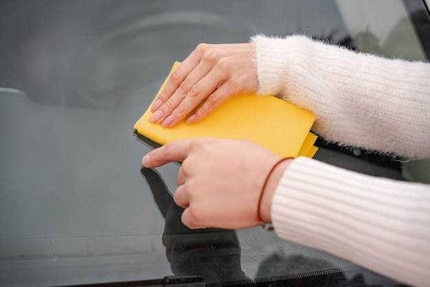 Couple cleaning car windshield with rag. man pointing with finger on glass for girl. close up of couple hands