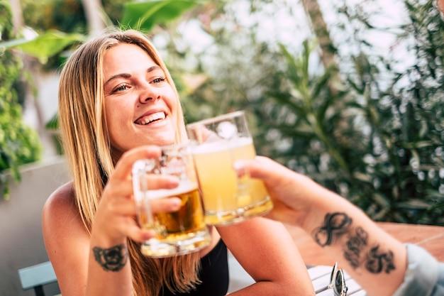 新鮮なおいしいビールを 1 パイント飲みながらバーで乾杯し、歓声を上げ、一緒に祝う友情を楽しむカップル