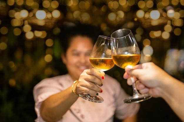 Пара звонит бокалом белого вина для празднования