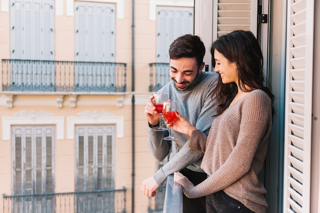Couple clinking glasses on balcony