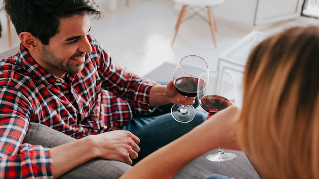 Couple clinking red wine on sofa