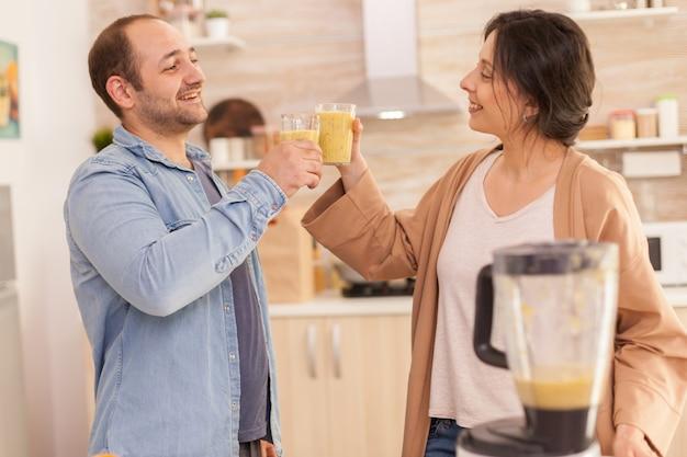 부엌에서 스무디 잔을 부딪치는 커플. 쾌활한 남자와 여자입니다. 건강하고 평온하고 쾌활한 생활 방식, 다이어트를 먹고 포근하고 화창한 아침에 아침 식사를 준비합니다.