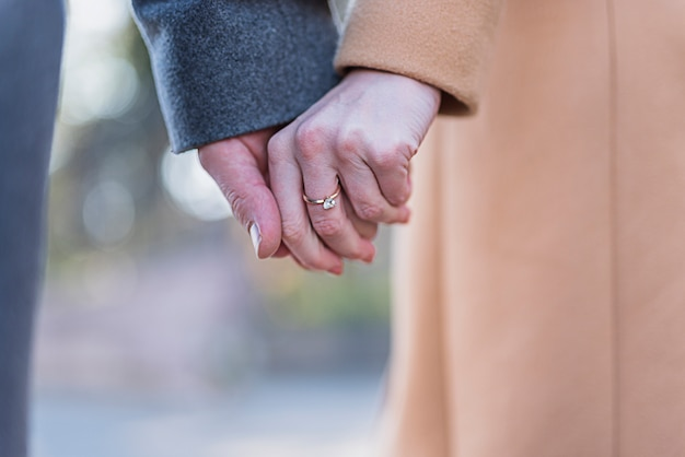 Couple in coats holding hands