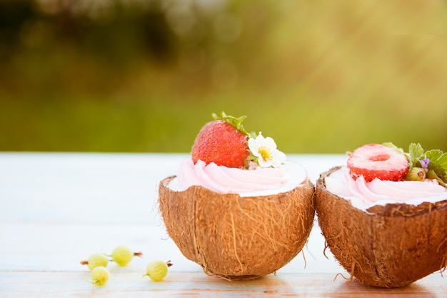 A couple of coconut cupcakes with flowers, strawberries and cheese cream