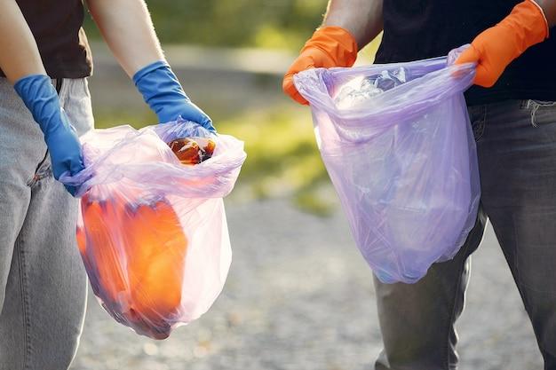 공원에서 쓰레기 봉투에 쓰레기를 수집하는 커플 무료 사진
