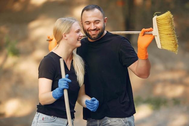 Пара собирает листья и убирает парк
