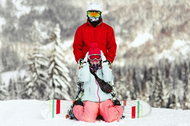 Coppia in abiti da sci colorati pone sulla collina da qualche parte nelle montagne