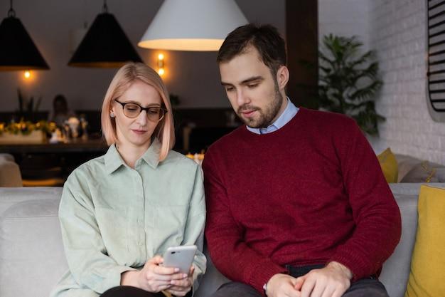 커플은 카페에서 의사 소통하고 스마트 폰으로 보입니다.