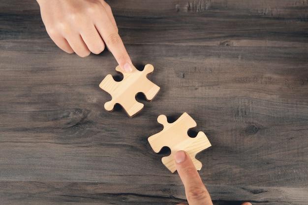 Пара соединяет кусочки пазла у стола