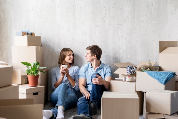 Couple conversing while having coffee and packing to move house