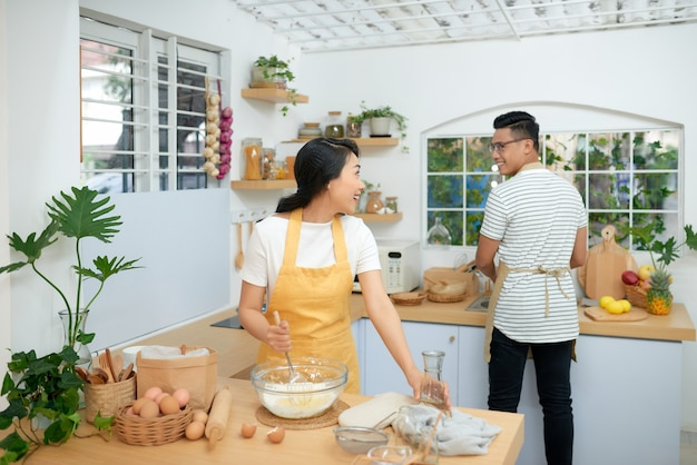 부엌 방에서 빵집을 요리하는 커플, 젊은 아시아 남자와 여자가 함께 케이크와 계란으로 빵을 만들고,
