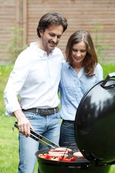 屋外のグリルで料理をするカップル