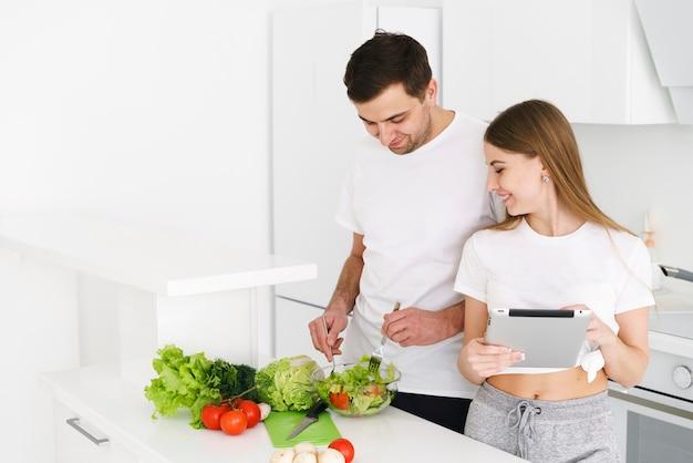 自宅で時間を調理するカップル