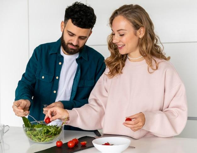 Coppie che cucinano insieme a casa