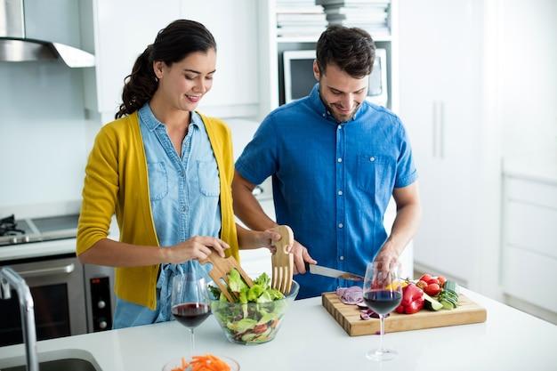 自宅のキッチンで一緒に料理をするカップル