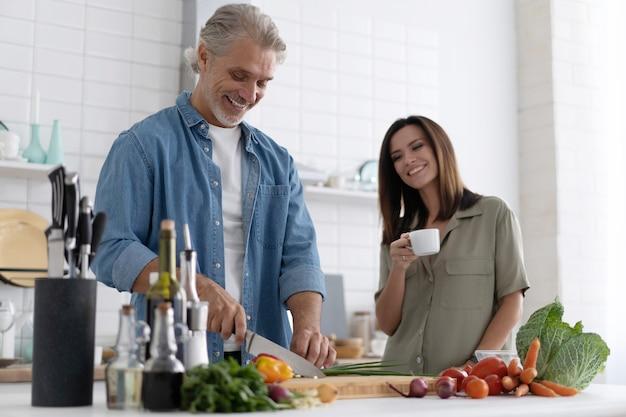 自宅のキッチンで一緒に料理をするカップル。