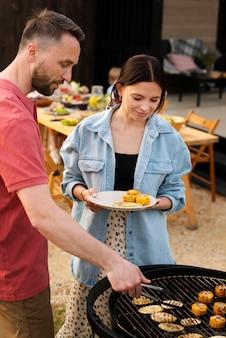 ミディアムショットを一緒に料理するカップル