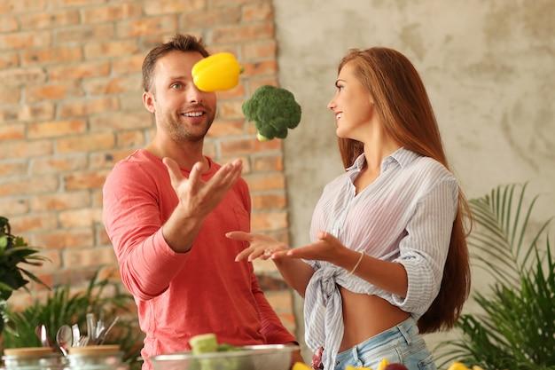 キッチンで野菜を調理するカップル