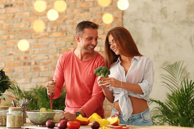 Пара готовит овощи на кухне