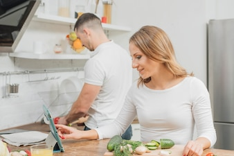 Couple cooking with tablet at home