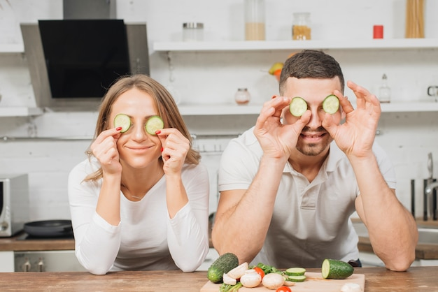 Couple covering eyes with cucumber