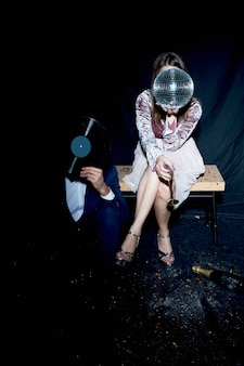 Couple covering faces with disco ball and vinyl record at party