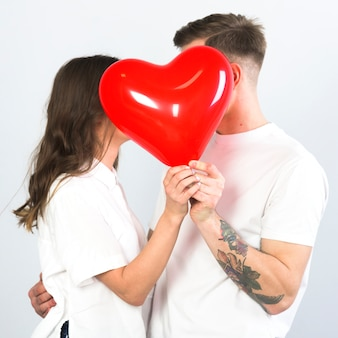 Couple covering faces with heart balloon