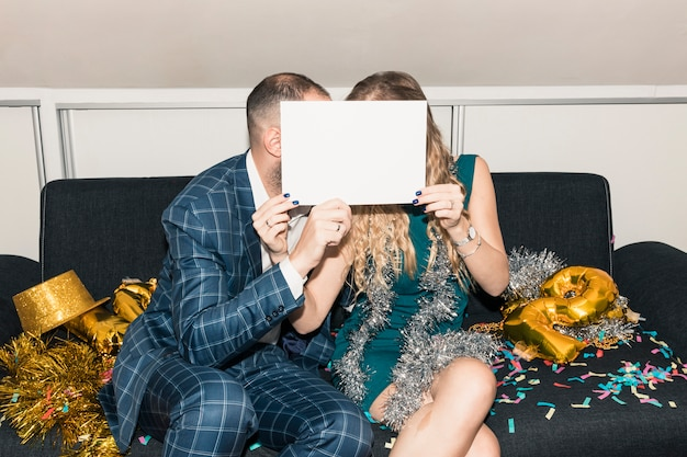 Couple covering faces with white paper on couch