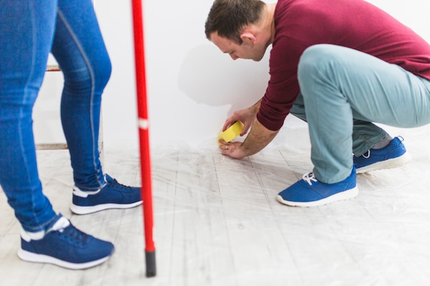Couple covering floor with protective sheet