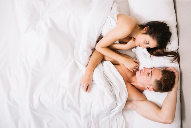 Couple cuddling in bed under white blanket