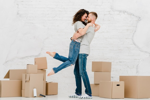 Couple cuddling near boxes