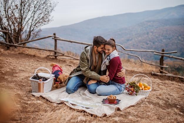 Couple cuddling at picnic.