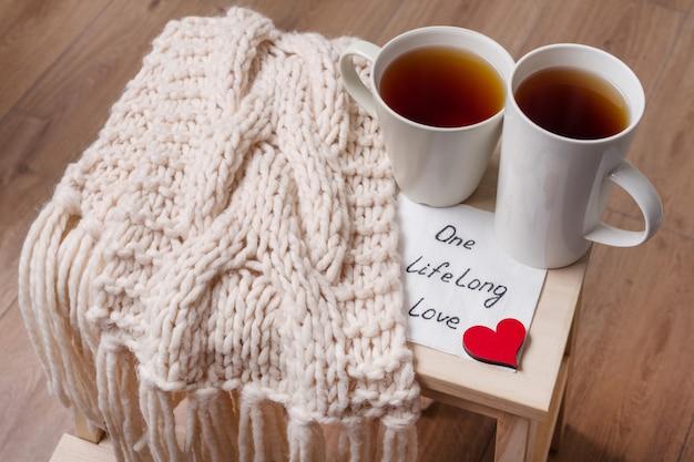 Couple of cups, warm scarf, in home interior