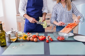 Couple cutting different vegetables on wooden board at table