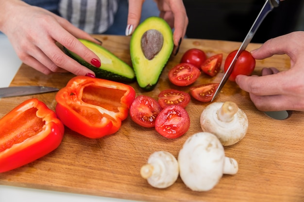 Couple cutting different vegetables on wooden board