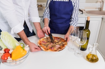 Couple cutting pizza on white table