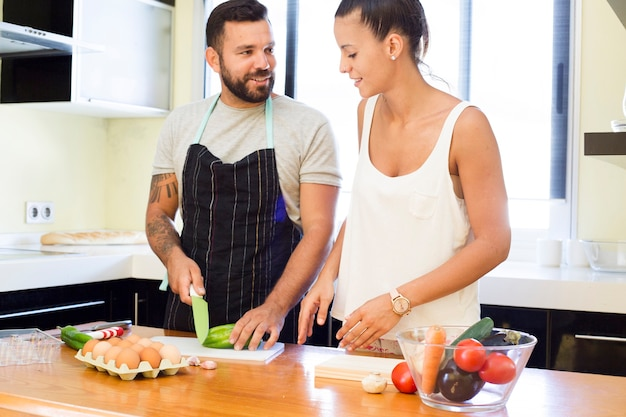 Couple cutting vegetable in kitchen