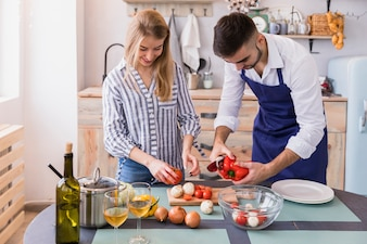 Couple cutting vegetables for salad on board